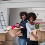 Smiling, young, multiethnic couple moving into a new home to illustrate moving tips and hacks
