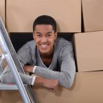young black man smiling and looking out from a stack of boxes to illustrate college moving