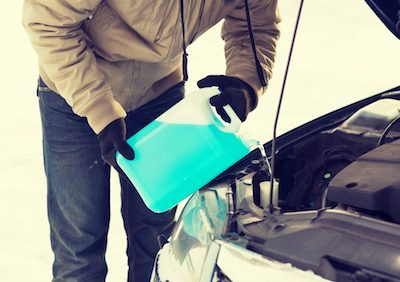 Man carefully pouring antifreeze into his car's radiator