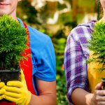 Man and woman holding plants