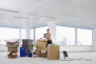 a woman boxing up office supplies and equipment