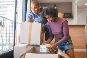 Young black couple unpacking at their new house to illustrate Questions To Ask Movers And Packers
