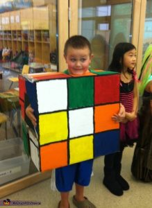 young boy wearing cardboard rubiks cube costume