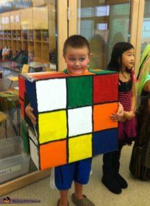 young boy wearing cardboard rubiks cube costume