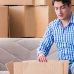 Young couple moving in to new house with boxes