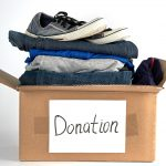 folded clothes and shoes in a brown donation box to illustrate Where to donate clothes in Portland OR